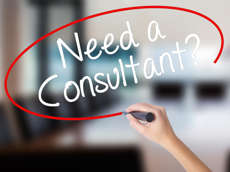 operational: Woman Hand Writing Need a Consultant? with a marker over transparent board. Isolated on Office. Business concept. Stock Photo