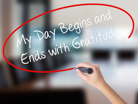 begins: Woman Hand Writing My Day Begins and Ends with Gratitude with a marker over transparent board. Isolated on Office. Business concept. Stock Photo Stock Photo