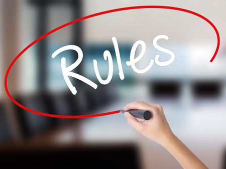 Woman Hand Writing Rules with a marker over transparent board. Isolated on Office. Business concept. Stock Photo