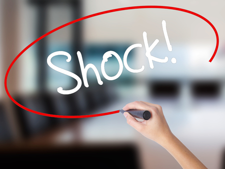Woman Hand Writing Shock! with a marker over transparent board. Isolated on Office. Business concept. Stock Photo