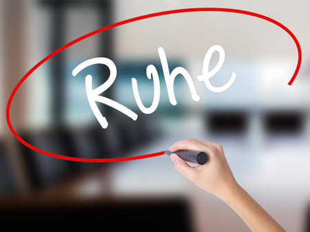 Woman Hand Writing Ruhe (Quiet in German) with a marker over transparent board. Isolated on Office. Business concept. Stock Photo