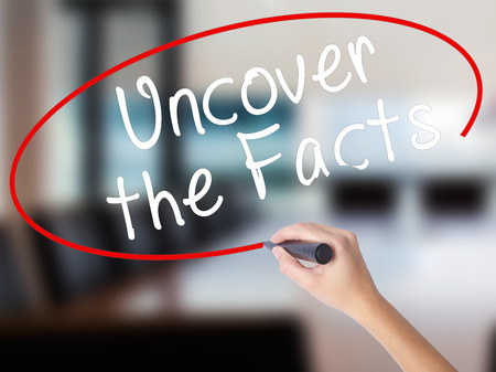 uncover: Woman Hand Writing Uncover the Facts with a marker over transparent board. Isolated on Office. Business concept. Stock Image