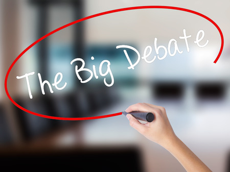 Woman Hand Writing The Big Debate with a marker over transparent board. Isolated on Office. Business concept. Stock Photo Stock Photo