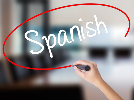 bilingual: Woman Hand Writing Spanish with a marker over transparent board. Isolated on Office. Business concept. Stock Photo