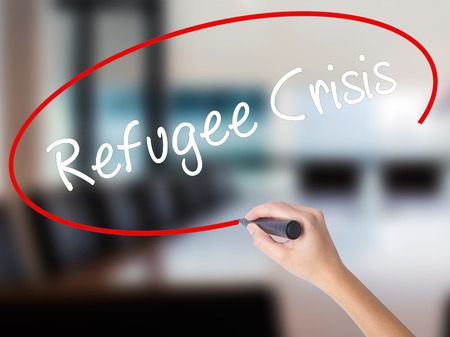 Woman Hand Writing Refugee Crisis with a marker over transparent board. Isolated on Office. Business concept. Stock Photo