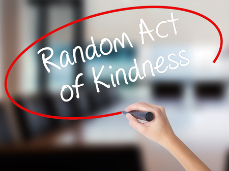 helping others: Woman Hand Writing Random Act of Kindness with a marker over transparent board. Isolated on Office. Business concept. Stock Photo