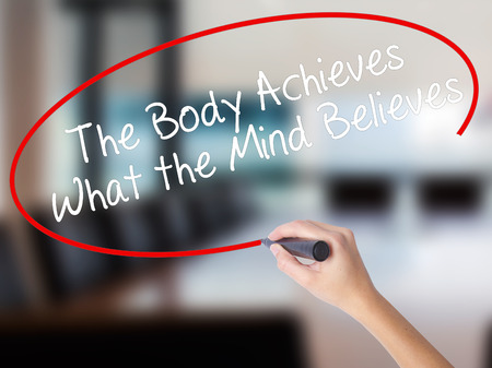 Woman Hand Writing The Body Achieves What the Mind Believes with a marker over transparent board. Isolated on Office. Business concept. Stock Photo