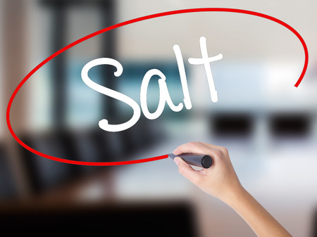 Woman Hand Writing Salt with a marker over transparent board. Isolated on Office. Business concept. Stock Photo
