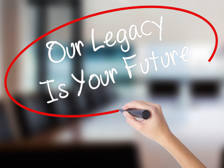impression: Woman Hand Writing Our Legacy Is Your Future  with a marker over transparent board. Isolated on Office. Business concept. Stock Photo