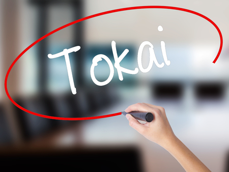 Woman Hand Writing Tokai with a marker over transparent board. Isolated on Office. Business concept. Stock Photo