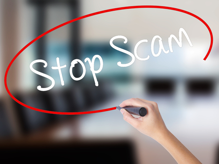 Woman Hand Writing Stop Scam with a marker over transparent board. Isolated on Office. Business concept. Stock Photo