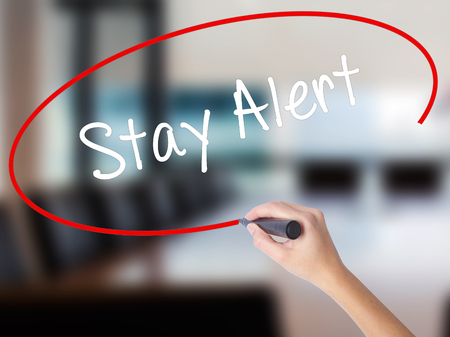 Woman Hand Writing Stay Alert with a marker over transparent board. Isolated on Office. Business concept. Stock Photo