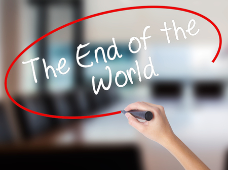 Woman Hand Writing The End of the World with a marker over transparent board. Isolated on Office. Business concept. Stock Photo