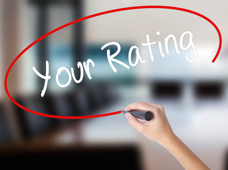 Woman Hand Writing Your Rating with a marker over transparent board. Isolated on Office. Business concept. Stock Photo