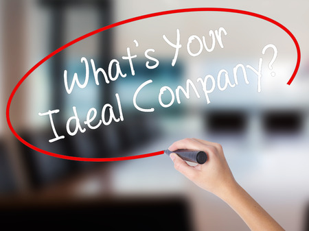 Woman Hand Writing Whats Your Ideal Company? with a marker over transparent board. Isolated on Office. Business concept. Stock Photo