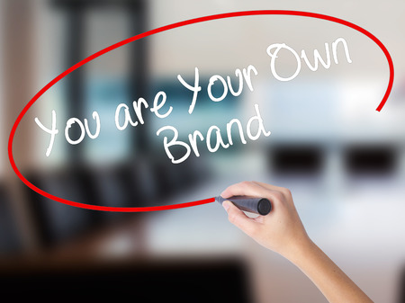 Woman Hand Writing You are Your Own Brand with a marker over transparent board. Isolated on Office. Business concept. Stock Photo