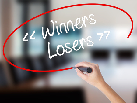 harass: Woman Hand Writing Winners - Losers  with a marker over transparent board. Isolated on Office. Business concept. Stock Photo