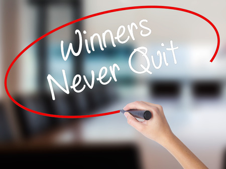 Woman Hand Writing Winners Never Quit with a marker over transparent board. Isolated on Office. Business concept. Stock Photo Stock Photo