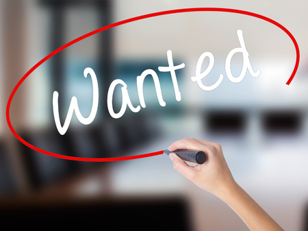 Woman Hand Writing Wanted with a marker over transparent board. Isolated on Office. Business concept. Stock Photo