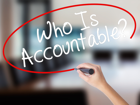 Woman Hand Writing Who Is Accountable? with a marker over transparent board. Isolated on Office. Business concept. Stock Image Stock Photo