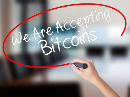 Woman Hand Writing We Are Accepting Bitcoins with a marker over transparent board. Isolated on Office. Business concept. Stock Photo Stock Photo
