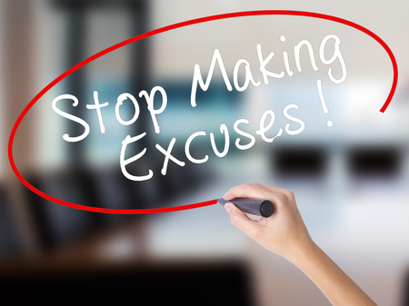 Woman Hand Writing Stop Making Excuses with a marker over transparent board. Isolated on Office. Business concept. Stock Image