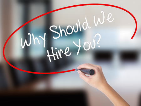 Woman Hand Writing Why Should We Hire You? with a marker over transparent board. Isolated on Office. Business concept. Stock Photo Stock Photo