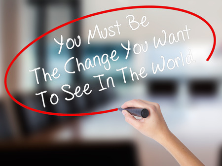 Woman Hand Writing You Must Be The Change You Want To See In The World with a marker over transparent board. Isolated on Office. Business concept. Stock Photo