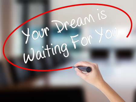 Woman Hand Writing Your Dream is Waiting For You with a marker over transparent board. Isolated on Office. Business concept. Stock Photo