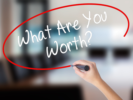 Woman Hand Writing What Are You Worth? with a marker over transparent board. Isolated on Office. Business concept. Stock Photo