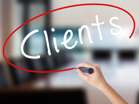 Woman Hand Writing Clients with a marker over transparent board. Isolated on Office. Business concept. Stock Image Stock Photo