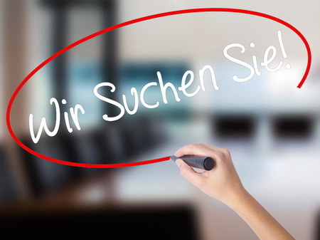 Woman Hand Writing Wir Suchen Sie! (Looking For You in German) with a marker over transparent board. Isolated on Office. Business,  technology, internet concept. Stock Photo