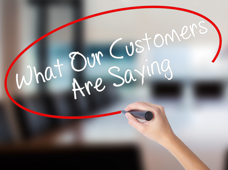 testimonials: Woman Hand Writing What Our Customers Are Saying with a marker over transparent board. Isolated on Office. Business concept. Stock Photo