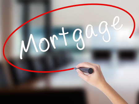 Woman Hand Writing Mortgage with a marker over transparent board. Isolated on Office. Business concept. Stock Image