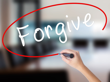 Woman Hand Writing Forgive with a marker over transparent board. Isolated on Office. Business concept. Stock Image Stock Photo