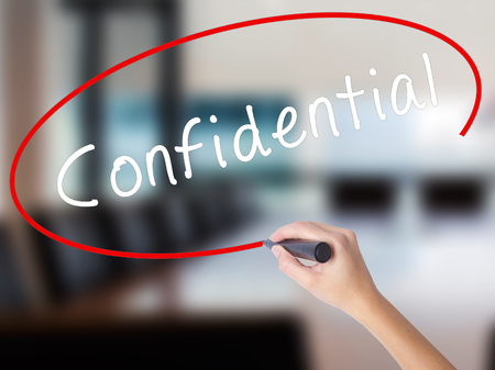 hushed: Woman Hand Writing Confidential with a marker over transparent board. Isolated on Office. Business concept. Stock Image Stock Photo