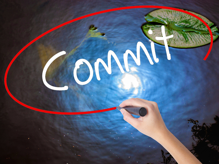 comité d entreprise: Woman Hand Writing Commit with marker over transparent board. Isolated on nature. Business concept. Stock Photo