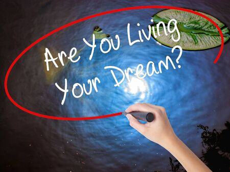 jargon: Woman Hand Writing Are You Living Your Dream? with marker over transparent board. Isolated on nature. Business concept. Stock Photo Stock Photo