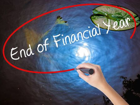 year financial statements: Woman Hand Writing End of Financial Year with marker over transparent board. Isolated on nature. Business concept. Stock Photo