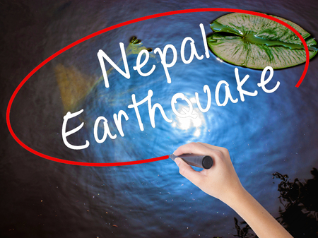 foothills: Woman Hand Writing Nepal Earthquake with marker over transparent board. Isolated on nature. Business concept. Stock Image