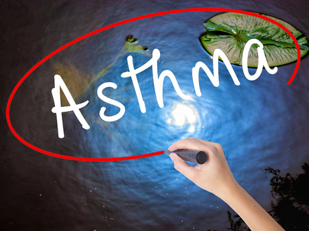 Woman Hand Writing Asthma with marker over transparent board. Isolated on nature. Business concept. Stock Image Stock Photo