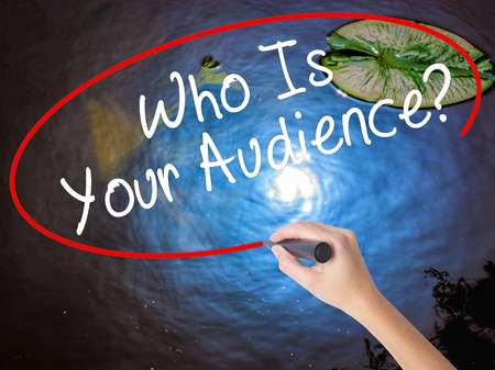 Woman Hand Writing Who Is Your Audience? with marker over transparent board. Isolated on nature. Business concept. Stock Image