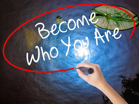 Woman Hand Writing Become Who You Are with marker over transparent board. Isolated on nature. Business concept. Stock Photo