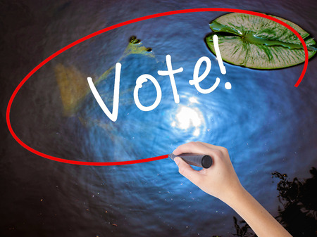 governing: Woman Hand Writing Vote! with marker over transparent board. Isolated on nature. Business concept. Stock Photo