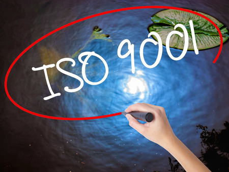 Woman Hand Writing  Iso 9001 with marker over transparent board. Isolated on nature. Business concept. Stock Photo