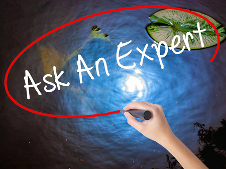 warranty questions: Woman Hand Writing Ask An Expert with marker over transparent board. Isolated on nature. Business concept. Stock Photo