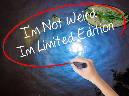 wacky: Woman Hand Writing Im Not Weird Im Limited Edition with marker over transparent board. Isolated on nature. Business concept. Stock Photo