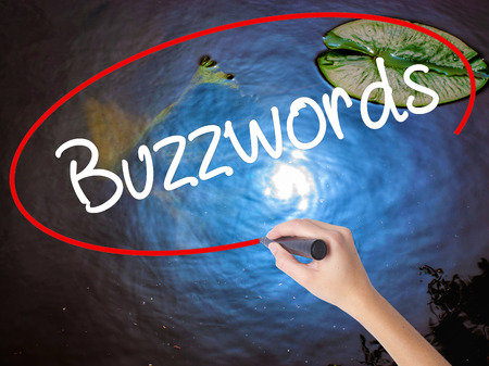 Woman Hand Writing Buzzwords with marker over transparent board. Isolated on nature. Business concept. Stock Photo
