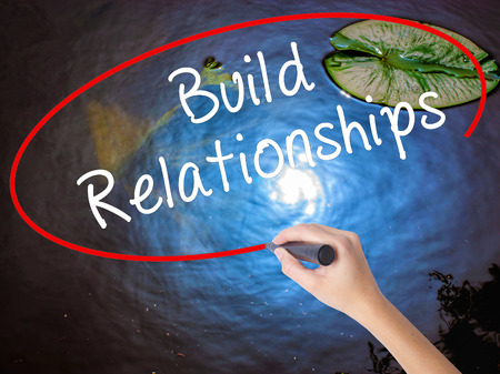 Woman Hand Writing Build Relationships with marker over transparent board. Isolated on nature. Business concept. Stock Image