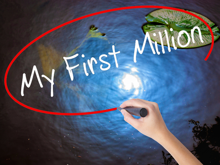 opulence: Woman Hand Writing My First Million with marker over transparent board. Isolated on nature. Business concept. Stock Image